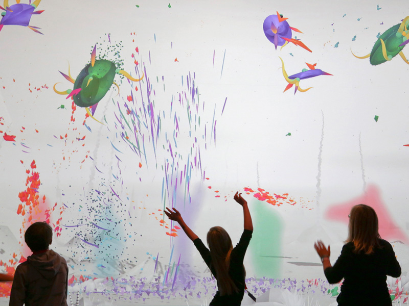 Kids play in front of an interactive animation wall.