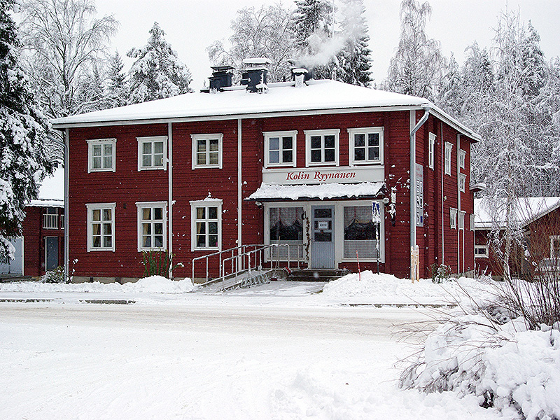 Red wooden house in winter landscape. There is a sign on the wall that says Kolin Ryynänen.