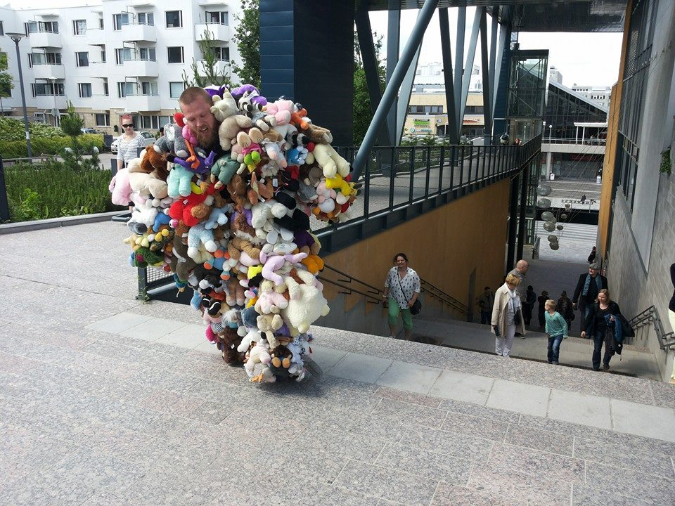 The artist is moving around in city-space dressed in a huge costume made of fluffy animals.