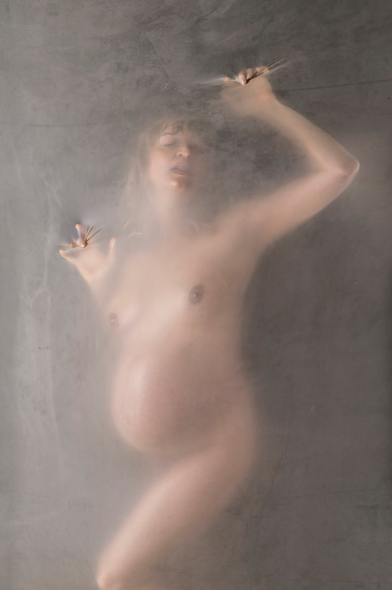 A naked pregnant woman leans on a see-through film.